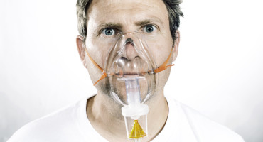 man wears nebulizer mask for asthma