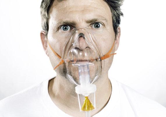 man wears nebulizer mask for asthma