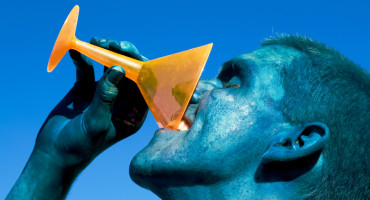 man covered in blue paint drinks from an orange glass