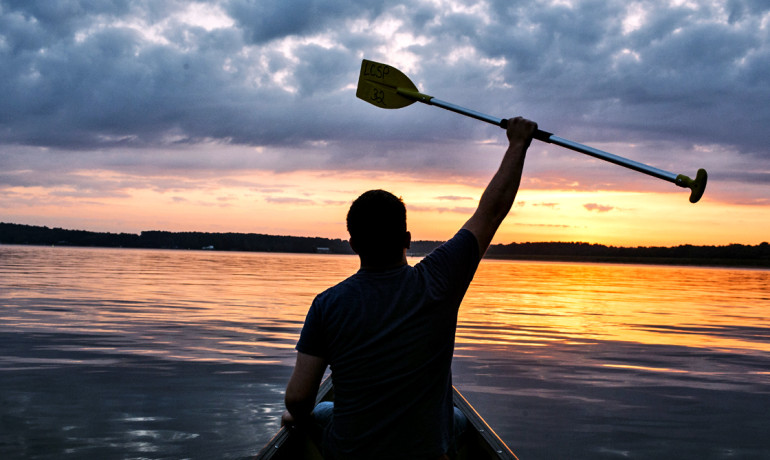 man in canoe at sunset