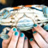 fingers with blue nail polish hold crab
