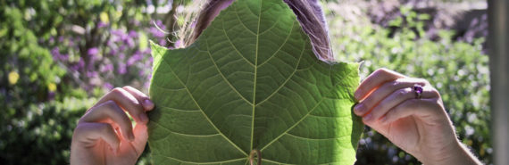 woman holds leaf over face