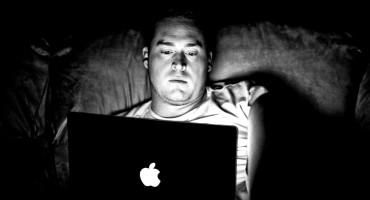 man's face in laptop glow