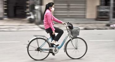 woman wearing a mask rides a bike
