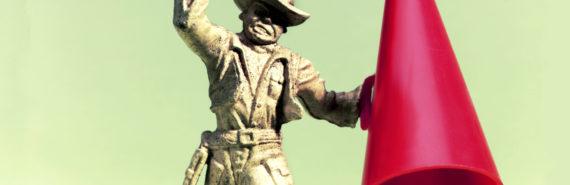 cowboy figurine holds red megaphone