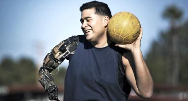 man with robot arm throws medicine ball