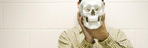 man in plaid shirt holds skull