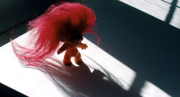 troll doll on desk casts shadow