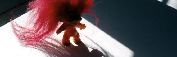 troll doll on desk casts shadow