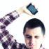 upset man holds phone, wears plaid