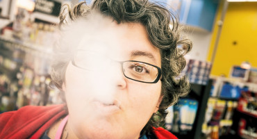 woman exhales e-cigarette vapor