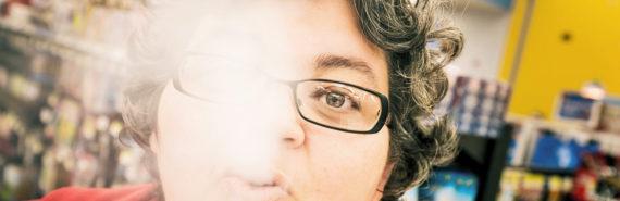 woman exhales e-cigarette vapor