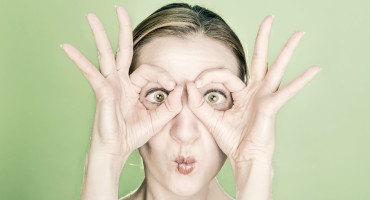 woman looks through hands to ogle