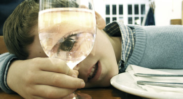 child looks through wine glass