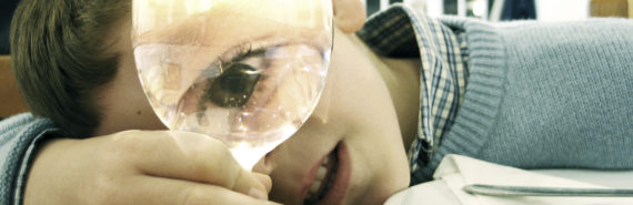 child looks through wine glass