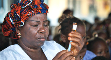 woman prepares measles vaccine in Guinea