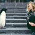 woman and penguin on city steps