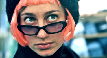 woman in pink wig looks over glasses