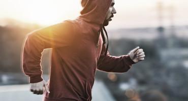man in red hoodie runs in city