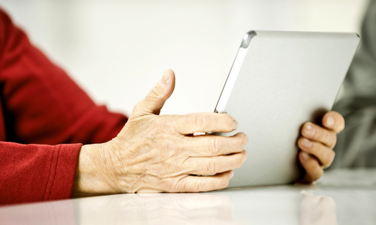 older adult in red shirt holds iPad