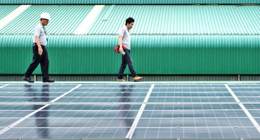 two men walk by solar cells