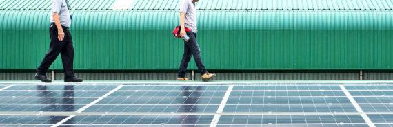 two men walk by solar cells