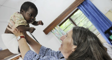 Terrie Taylor holds up baby in Malawi