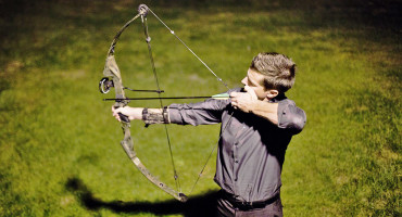 man shoots bow and arrow
