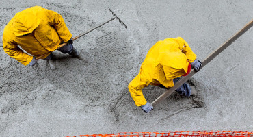 workers pouring concrete in yellow coats