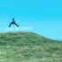 teen guy jumps on a hill