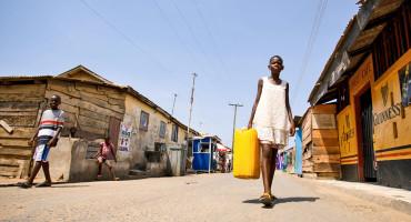 girl in Ghana carries drinking water
