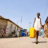 girl in Ghana carries drinking water