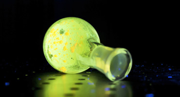 glowing green polymer in flask