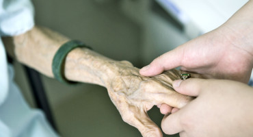 caregiver holds elderly woman's hand