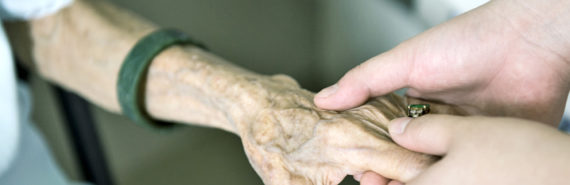 caregiver holds elderly woman's hand