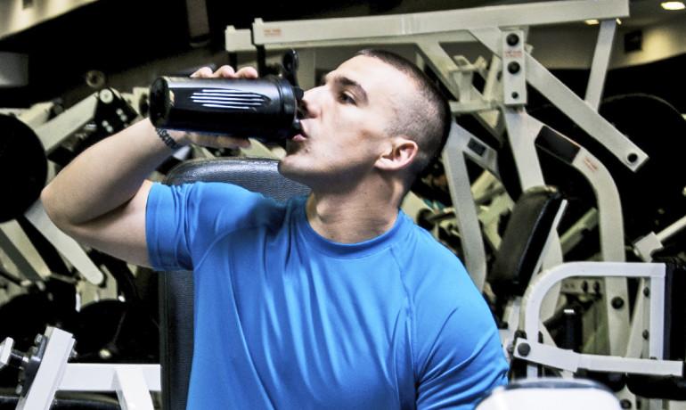 man at gym drinks supplement
