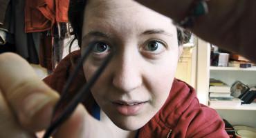 woman holds tweezers