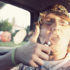 young man smoking in a car