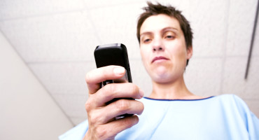 woman texts in hospital