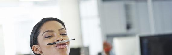 woman balances a pen on her lips