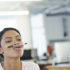 woman balances a pen on her lips