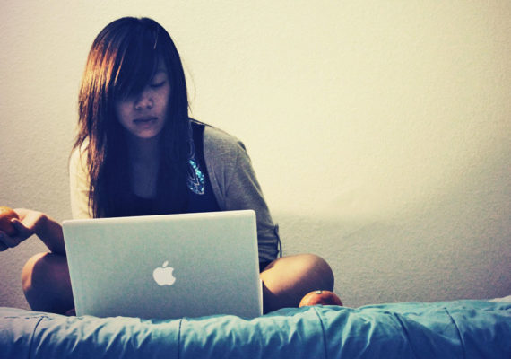 woman with laptop and oranges on bed