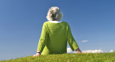woman with white hair sits on grass