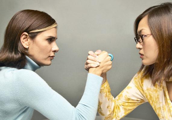 two women arm wrestle