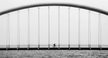 b/w lone biker on bridge