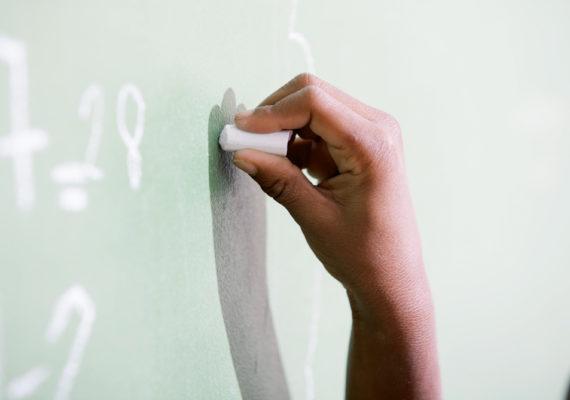 child's hand writes on chalkboard