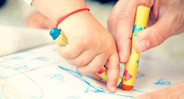 toddler & adult hands with crayons