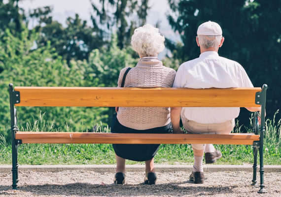 older couple sits on a bench