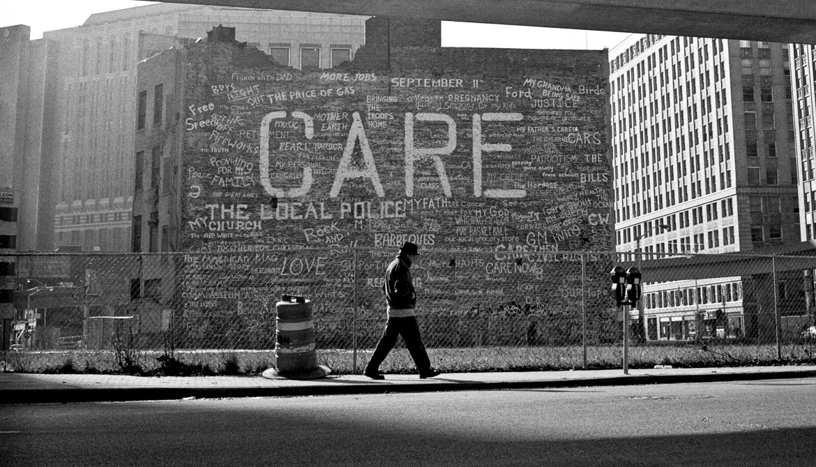 man walks by CARE sign in Detroit