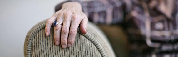 elderly woman's hand on sofa